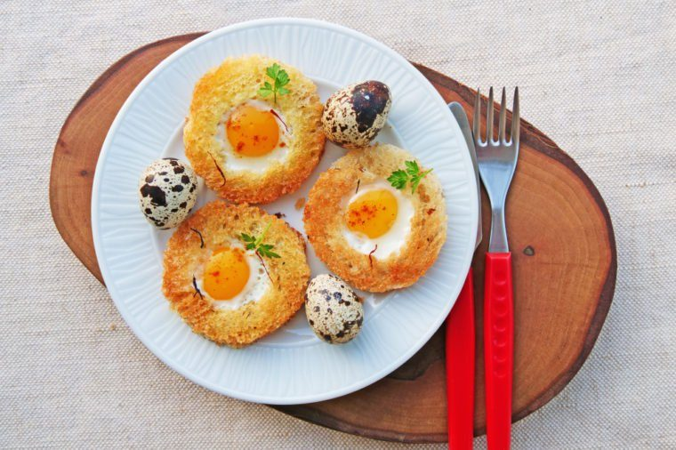 Egg in a basket with quail eggs and saffron on white plate top view