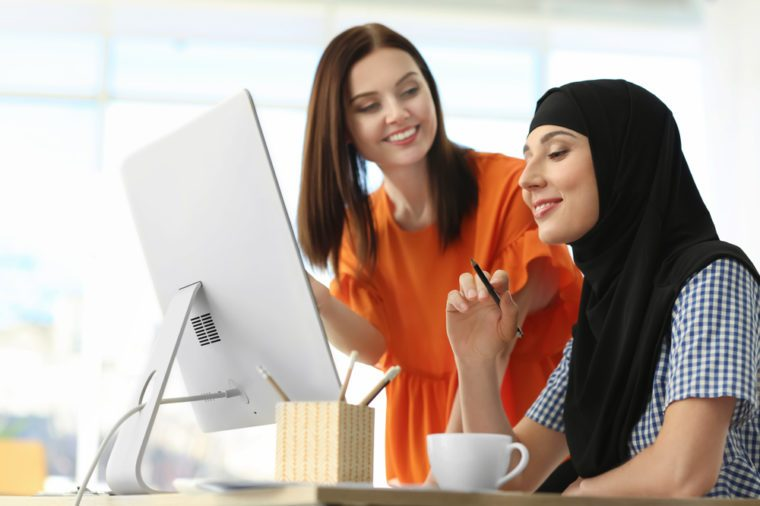 Muslim businesswoman with coworker in office
