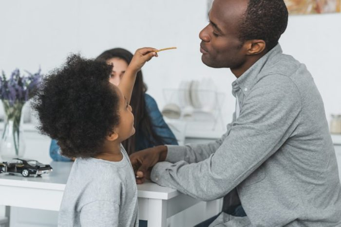 african american son feeding father with crispy breadsticks at home
