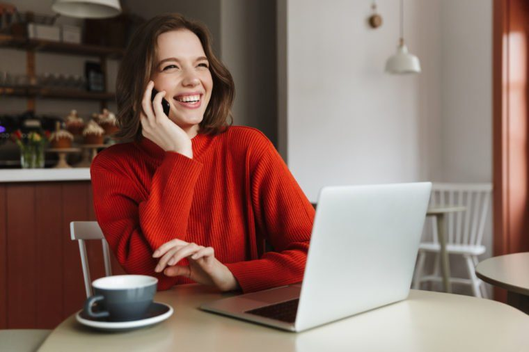 Image of happy caucasian woman 20s laughing and talking on smartphone while using laptop in cafe
