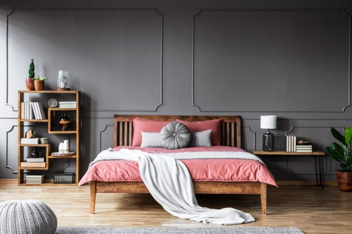 A large bed in a spacious, dark bedroom standing between a shelf with books and ornaments and a bedside table with lamp