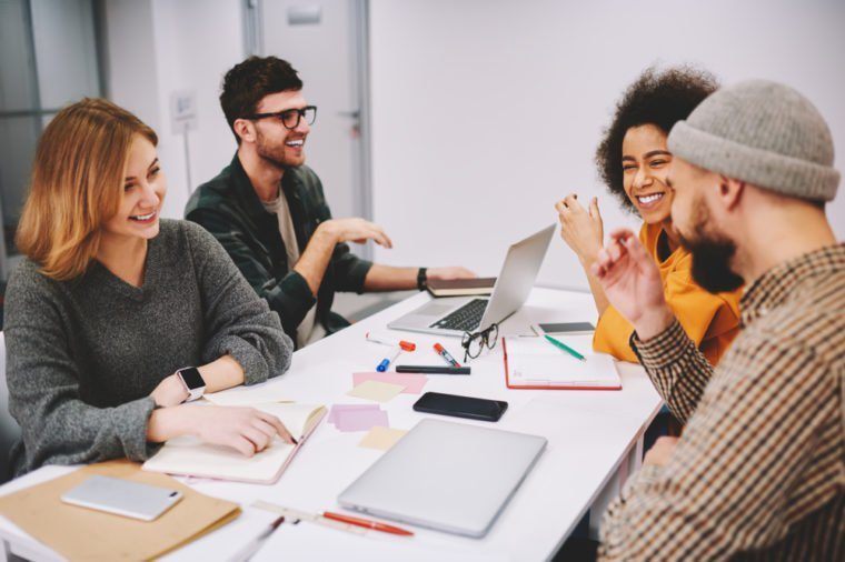 Positive male and female designers discussing creative ideas for developing startup project teamworking in office.Diversity group of cheerful hipsters students laughing during collaboration at desktop