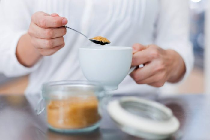 Woman hands serving sugar on coffee cup