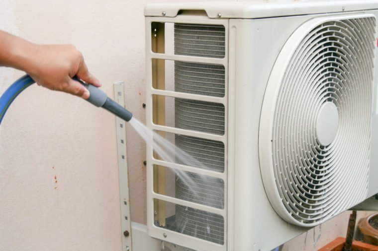 The men are cleaning the air conditioning condenser