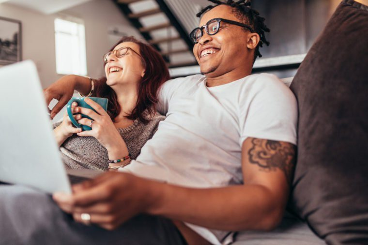 Cheerful multi-ethnic couple relaxing together on sofa with laptop and cup coffee. Smiling man and woman sitting on couch at home.