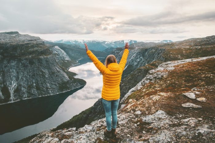 Happy woman raised hands on mountain summit traveling alone adventure lifestyle journey vacations aerial lake landscape success wellness emotions