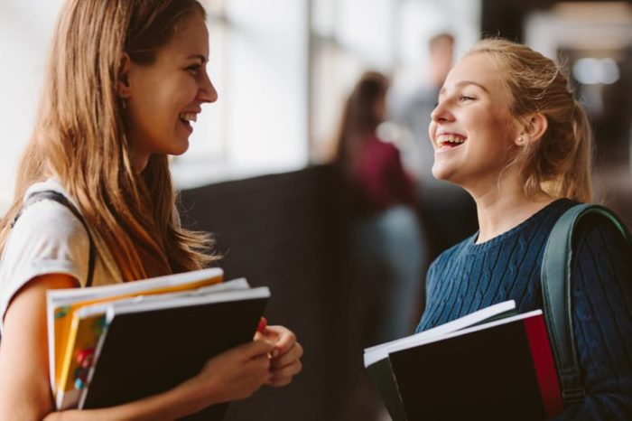 Two college students standing in corridor and chatting after their class. Two female college students talking and laughing after lecture.