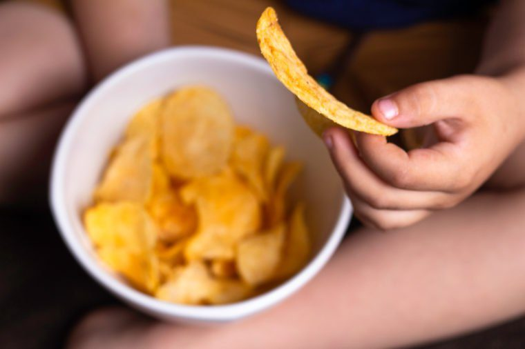 child's hand holds potato chips, concept of harmful food, fast food, obesity