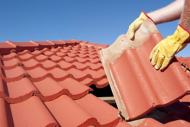 Roof repairs, worker with yellow gloves replacing red tiles or shingles on house with blue sk