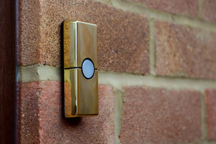 Gold or brass coloured doorbell on the brick wall of a house