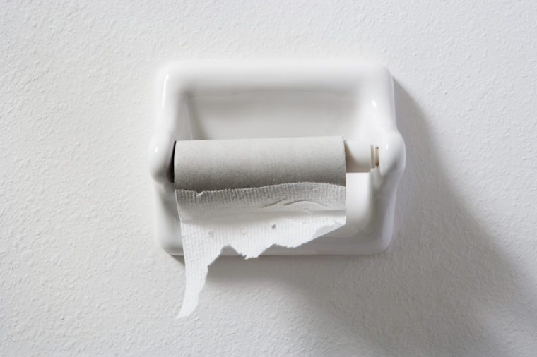 empty toilet paper roll on white wall