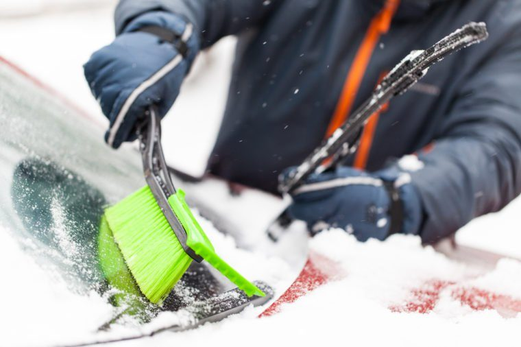 Transportation, winter, weather, people and vehicle concept - man cleaning snow from car with brush