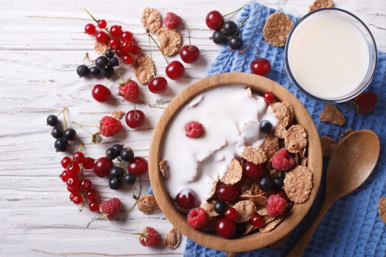 cereal with milk and fresh berries in a wooden bowl. horizontal view from above