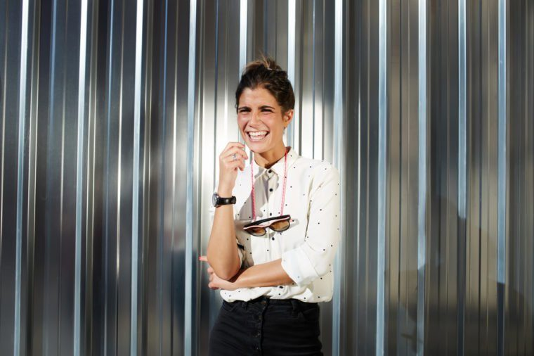 Young happy female hipster dressed in trendy clothing stand against copy space background, glamorous woman in stylish laughing brightly while posing against metallic chrome wall outdoors in sunny day