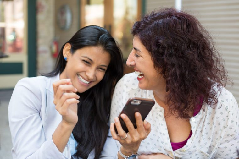 Closeup portrait two surprised girls looking at cell phone, discussing latest gossip news, sharing intimate moments, shopping, laughing at what they see, isolated outdoors background