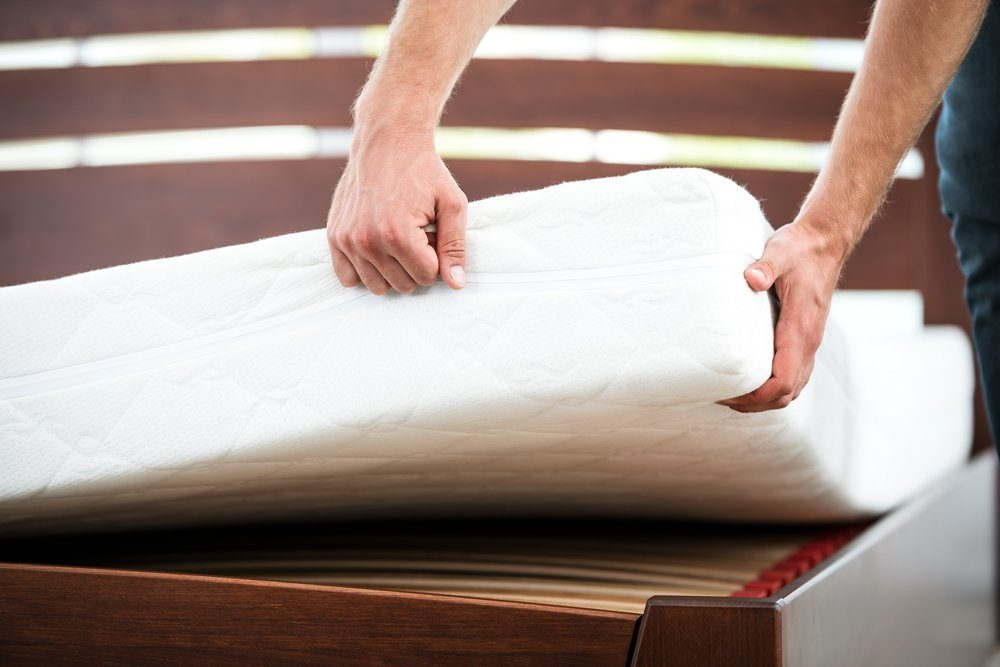 Close up photo of young man demonstrating quality of mattress