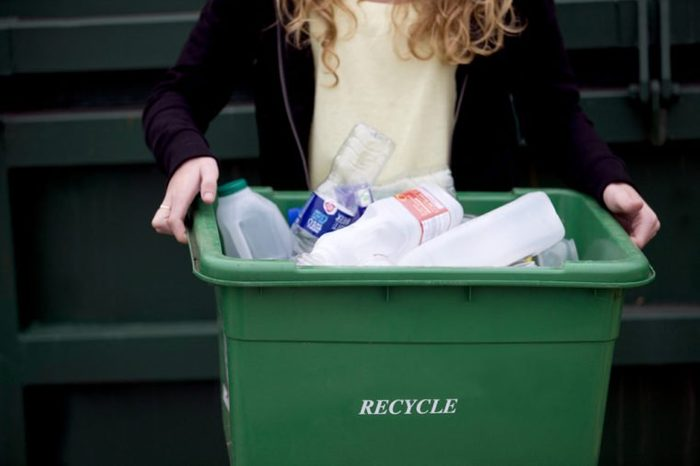 A teenage girl holding a recycling container