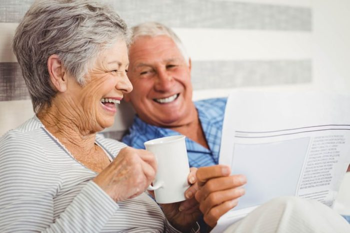 Senior couple laughing while reading newspaper in bedroom