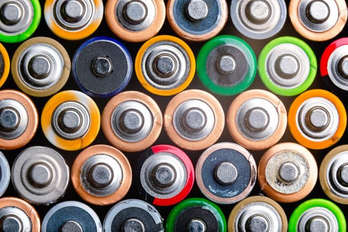 Energy abstract background of colorful batteries. Close up top view on rows of selection of AA batteries. Alkaline battery aa size. Several batteries are next to each other. Many aa batteries.