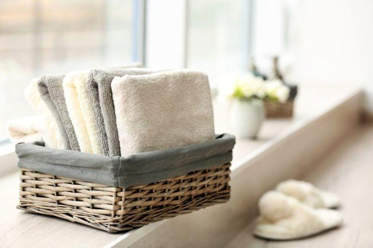 Towels in wicker basket with flowers on windowsill