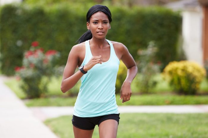 Young black woman in sports clothes running in the street