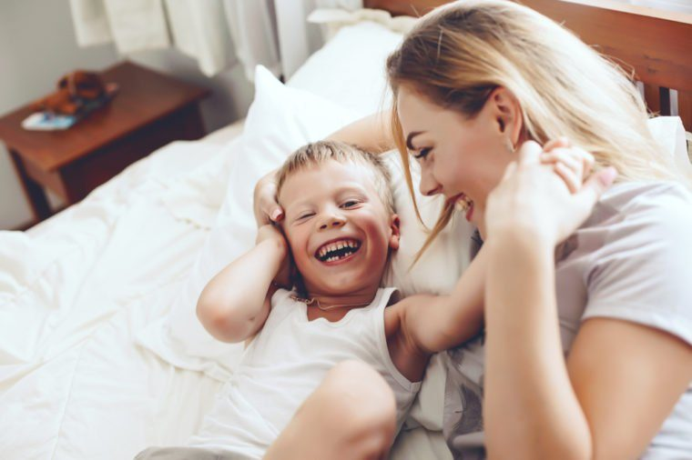 Young mother with her 6 years old little son dressed in pajamas are relaxing and playing in the bed at the weekend together, lazy morning, warm and cozy scene.