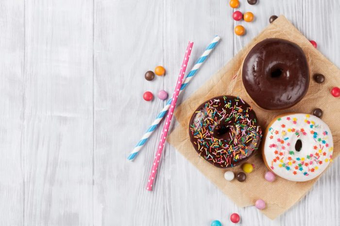 Colorful donuts on wooden table. Top view with copy space