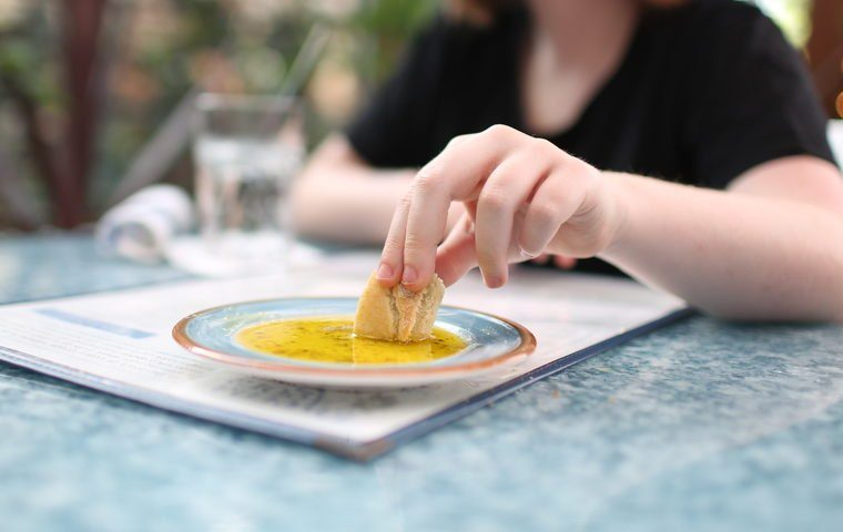 Hand dipping bread in olive oil