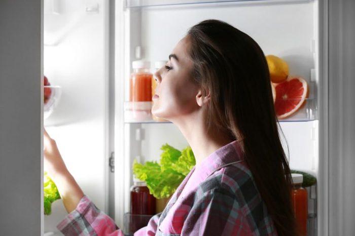 Young beautiful woman looking into fridge at night