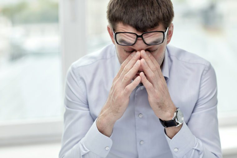 business, people and work concept - tired businessman with eyeglasses in office