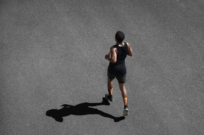 Top view of African runner wearing black sportswear training on black pavement at central position. Muscular fit sport model exercising sprint on city road. Full body length of dark-skinned sprinter