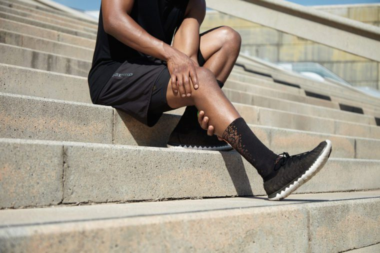 Sports injury concept. Cropped portrait of black male runner wearing black training outfit touching his leg in pain with clasped hands, having sprain or twitch in his knee after running exercises