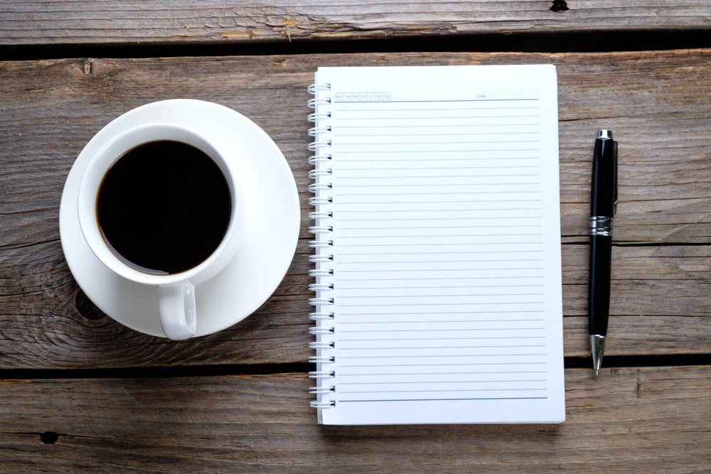 Blank notebook, coffee on rustic wooden background