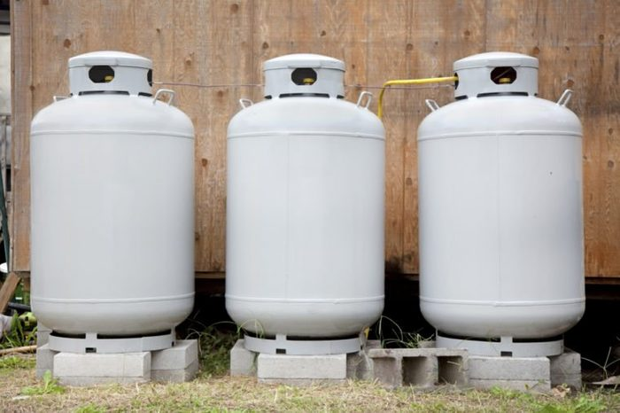 Front view of three gray propane tanks. Freshly painted. Horizontal.