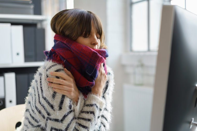 Sick businesswoman with winter chills and a fever sitting shivering in the office wrapped in a thick woolly winter scarf