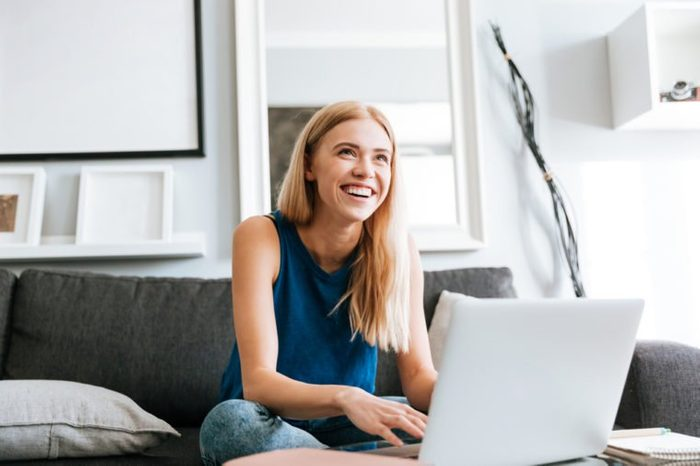 Cheerful cute young woman using laptop and laughing at home