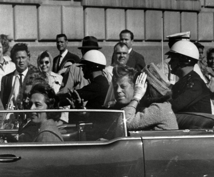 President John F. Kennedy riding in motorcade with first lady Jacqueline Kenndy