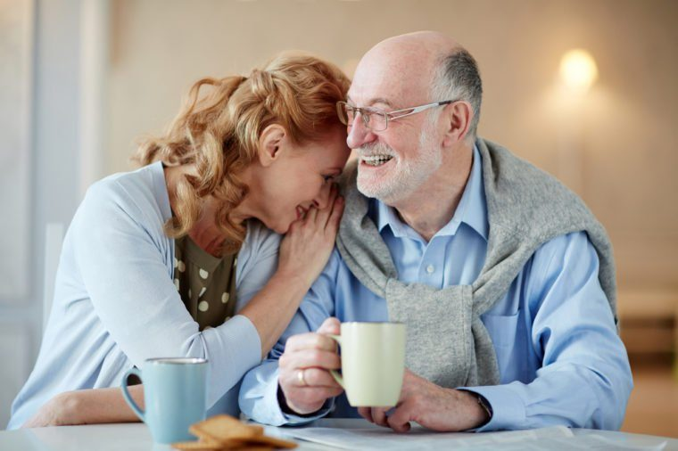 Portrait of smiling senior couple sitting close together cuddling caringly and laughingat kitchen table with tea cups and homemade cookies