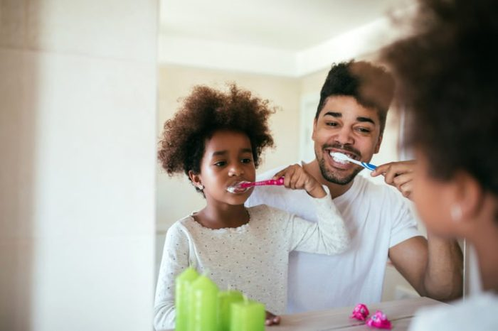 Portrait of happy african american father and daughter brushing teeth in the bathroom.