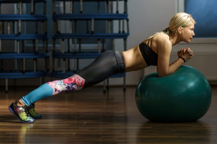 Sporty female in a fitness gym doing abs workout with a ball