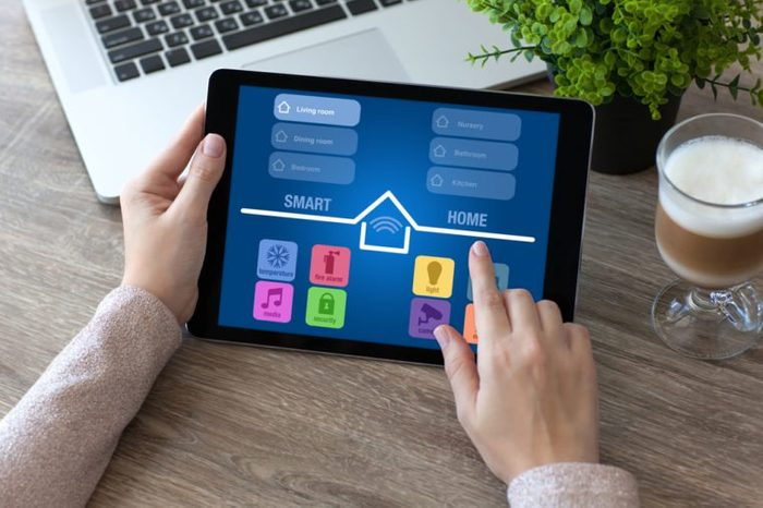 woman hands holding tablet computer with app smart home in room