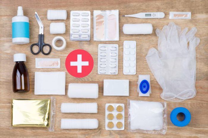 First aid kit on wooden background, top view