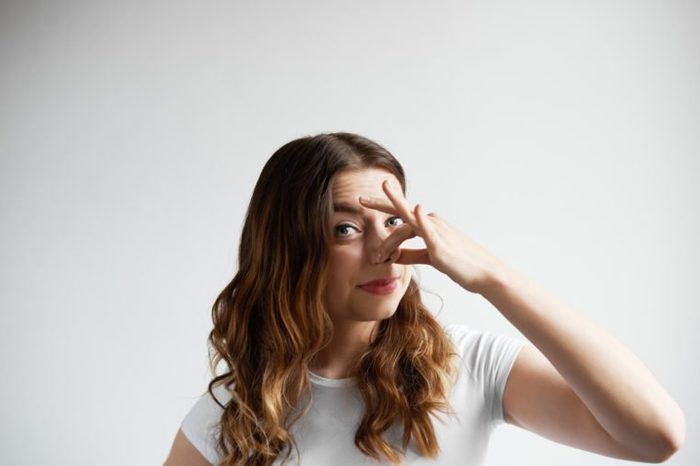 Bad smelling concept. Studio shot of disgusted young European woman pinching her nose because of awful stink coming out from garbage or spoiled food. Negative human emotions and nasty feelings.