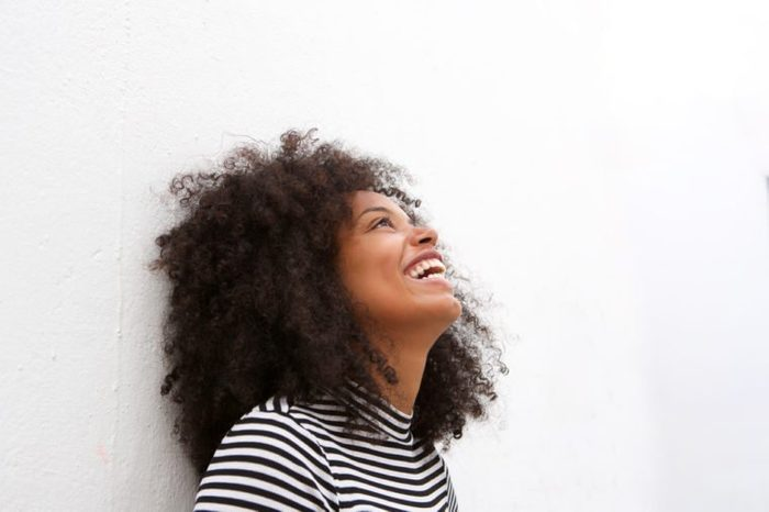 Close up side portrait of happy african american woman laughing