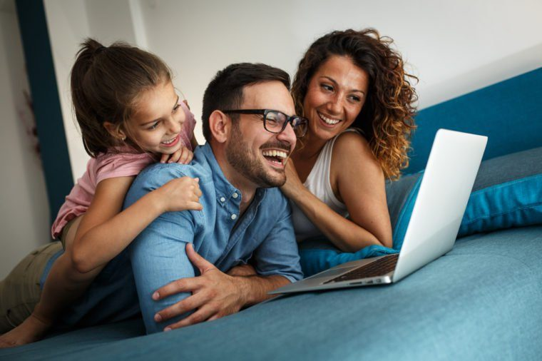 Happy family lies on bed and watching something on laptop.Laughing and fun.