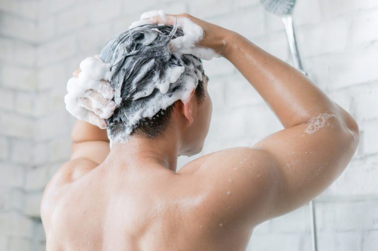 The man is washing his hair, he use shampoo.