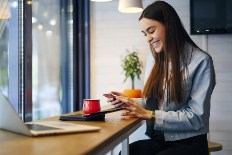 Positive young woman reading funny sms message on modern smartphone and laughing while sitting in cafe interior at table with laptop computer and notepad.Smiling female chatting in social networks