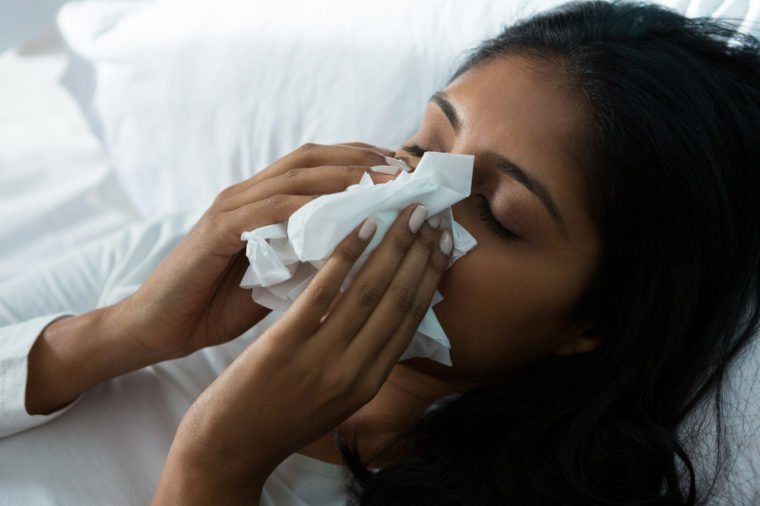 Woman blowing nose while relaxing on bed at home