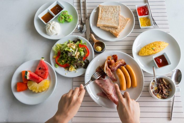 top view of a woman having big breakfast and some fruits