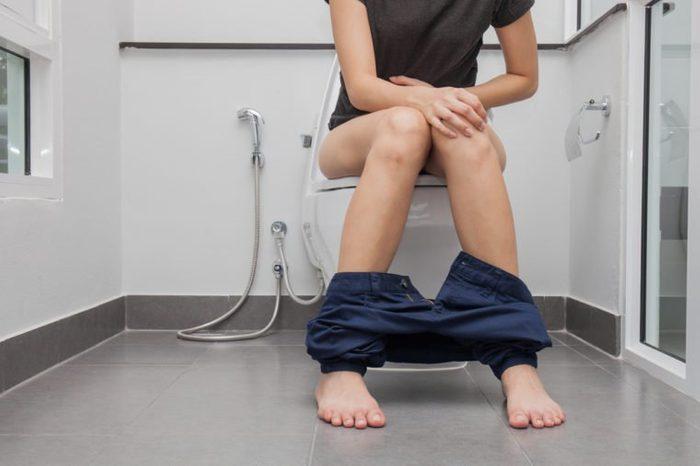 woman in bath towel sitting on toilet bowl
